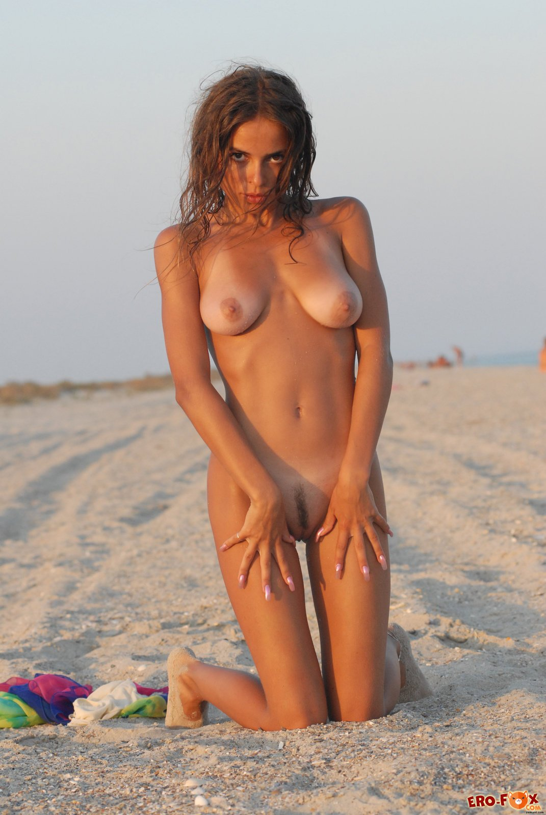 Грудастая девушка загорает на песке фото 91-751